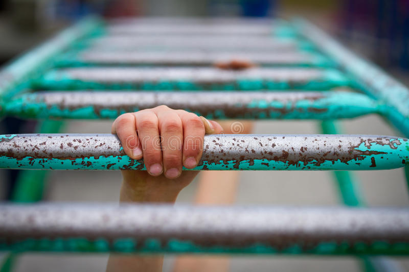 Hang on. Boy / child at school playground trying to hang on the monkey bars royalty free stock photography