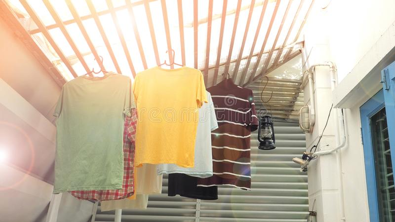 Hang the clothes on the roof batten in house. Hang the clothes are t-shirt hanging on the roof batten under the sun in my house stock images