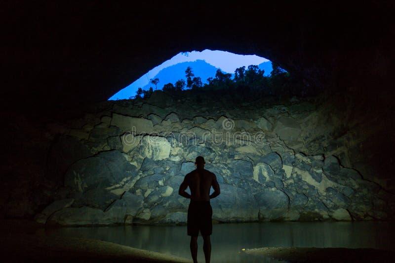 Hang En Cave - silhueta do homem que está dentro caverna a maior do mundo da ó em Vietname imagem de stock