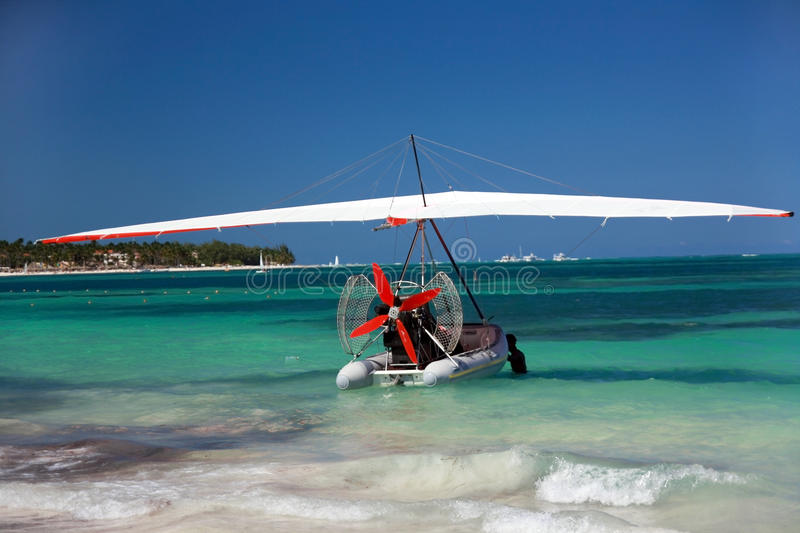 Hang glider on caribbean ocean stock images