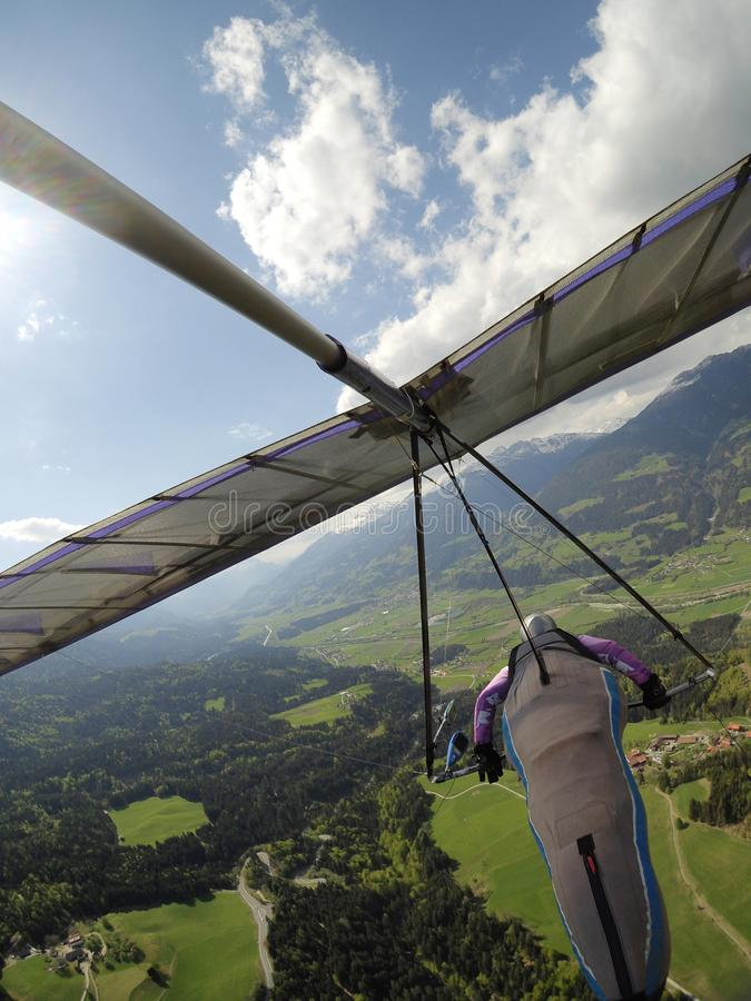 Hang glider pilot fly over green valley in Austria. Popular place for extreme sports royalty free stock photography