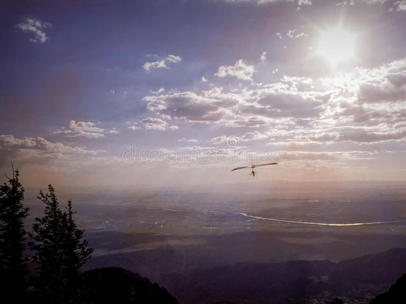 A Hang Glider Soars the Rio Grande Valley in New Mexico. The hot July sun in New Mexico generates thermals off the valley floor that hang gliders can ride for stock photography