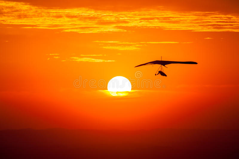 Hang gliding silluete. Hang gliding in the sunset royalty free stock photo