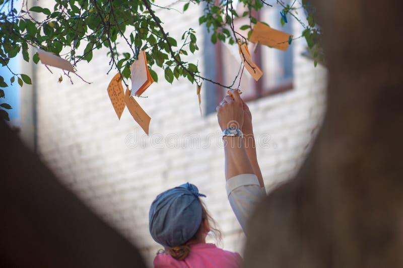 Hang nota's met wensen op een boom, nota's van oranje kleur stock fotografie