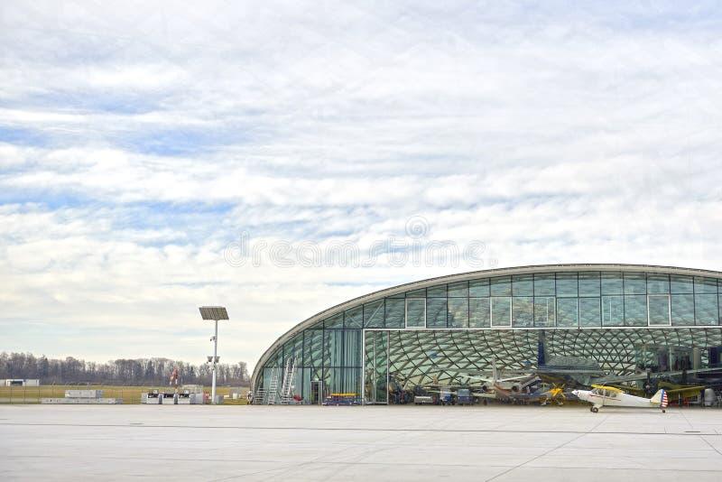 Hangar avec l'avion et le ciel bleu Un petit avion se tient près du hangar et prépare pour décoller Hangar de verre photo stock