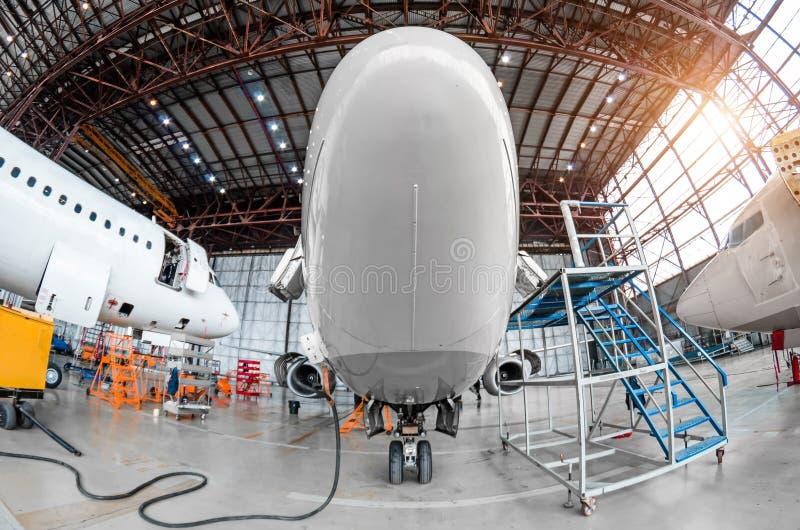 Hangar d'aviation avec l'avion, train d'atterrissage avant en gros plan du train d'atterrissage d'avion sur la réparation d'entre photo stock