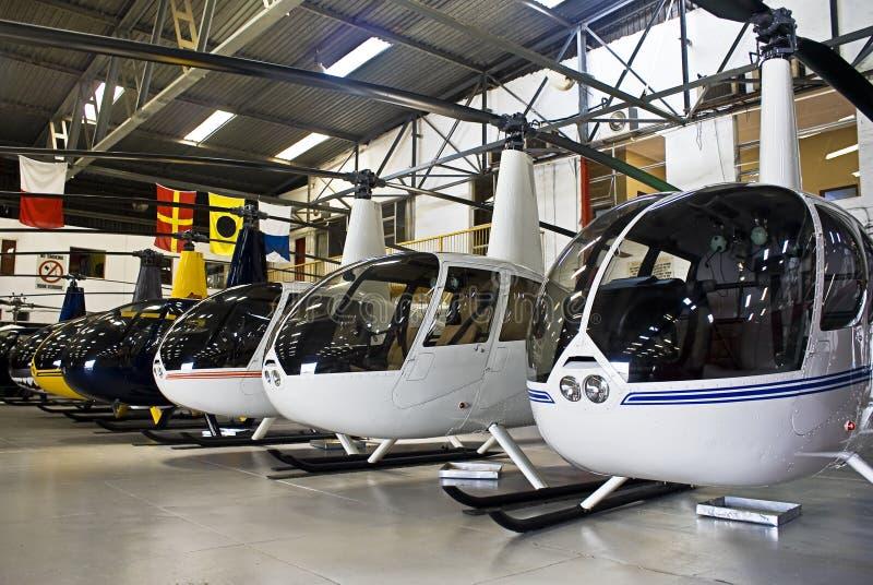 Hangar d'hélicoptère, plein de Robinson R44 photos libres de droits