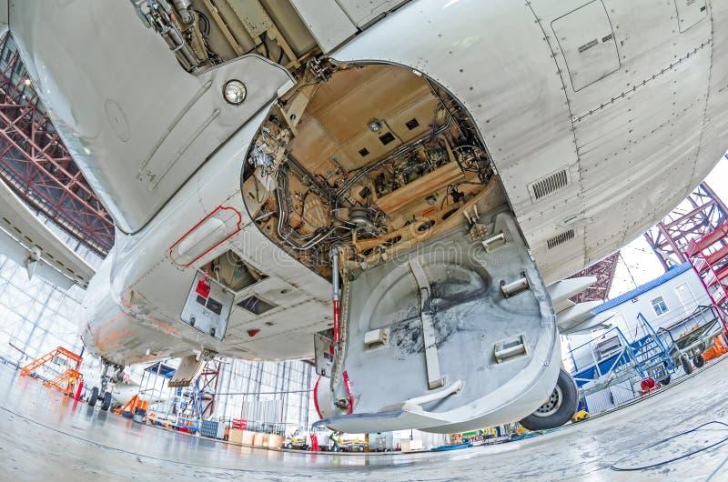 Hangar de la aviación con el aeroplano, tren de aterrizaje del primer del tren de aterrizaje de aeroplano en la reparación del ma fotos de archivo