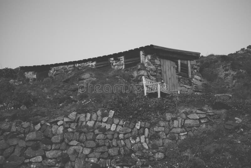 Hangar de pierre et en bois construit dans le flanc de coteau rocheux photos libres de droits