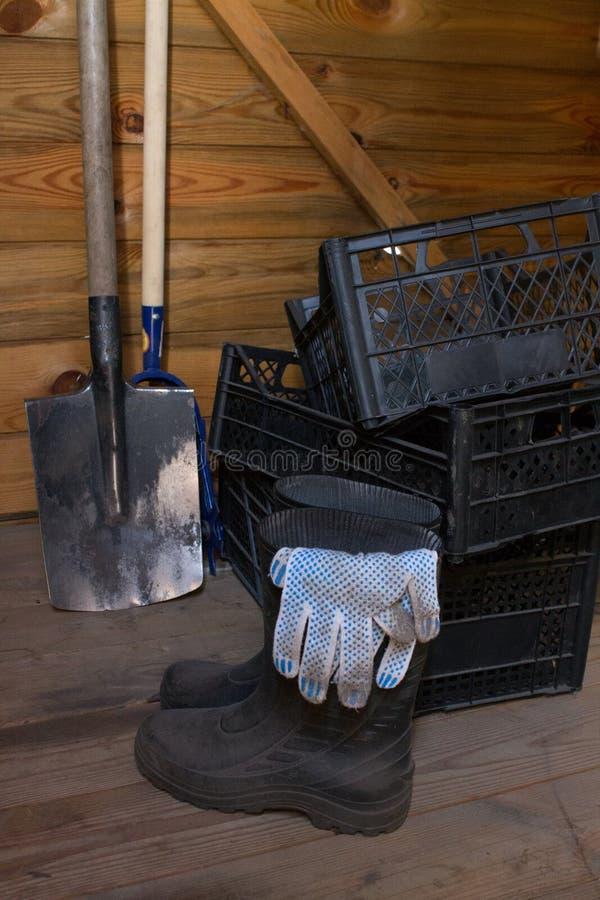 Hangar en bois avec les bottes en caoutchouc et la pelle de tiroirs en plastique vides photo libre de droits