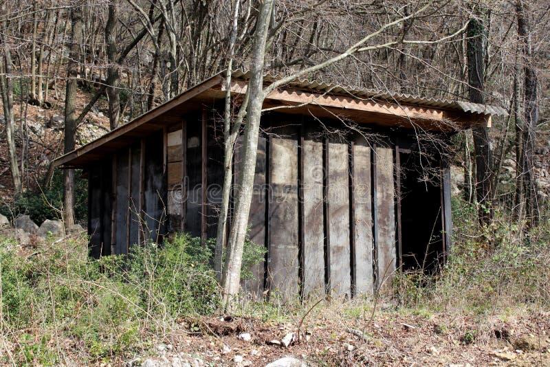 Hangar en bois improvisé d'outil d'arrière-cour fait à partir des conseils criqués au chantier de construction abandonné entouré  image libre de droits