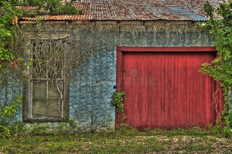 Hangar envahi avec la porte en bois rouge photo libre de droits