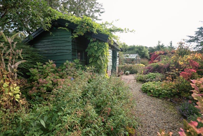Hangar et serre chaude de jardin entourés par un beau décoratif image libre de droits