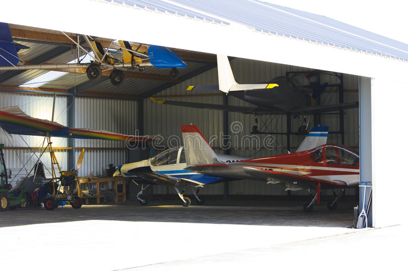 Hangar with ultralight planes. Open hangar with ultralight airplanes inside stock photo