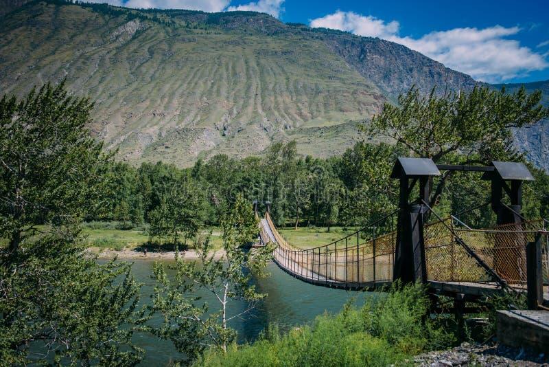 Hangbrug over de bergrivier De hangende die brug door weelderige groene bomen op de achtergrond van bergen wordt omringd en royalty-vrije stock foto's