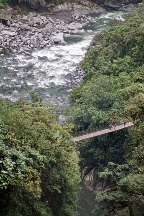Hangbrug over de rivier onder Pailon del Diablo Waterfall stock fotografie