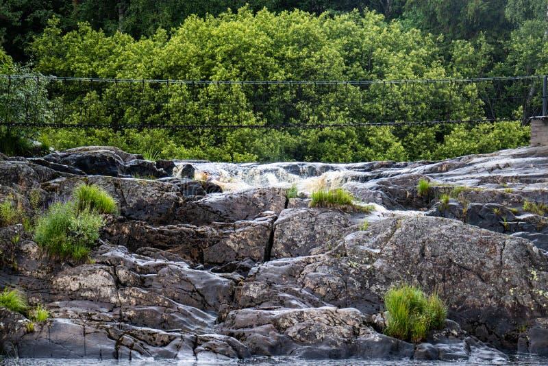 Hangbrug over een bergrivier met een waterval royalty-vrije stock fotografie