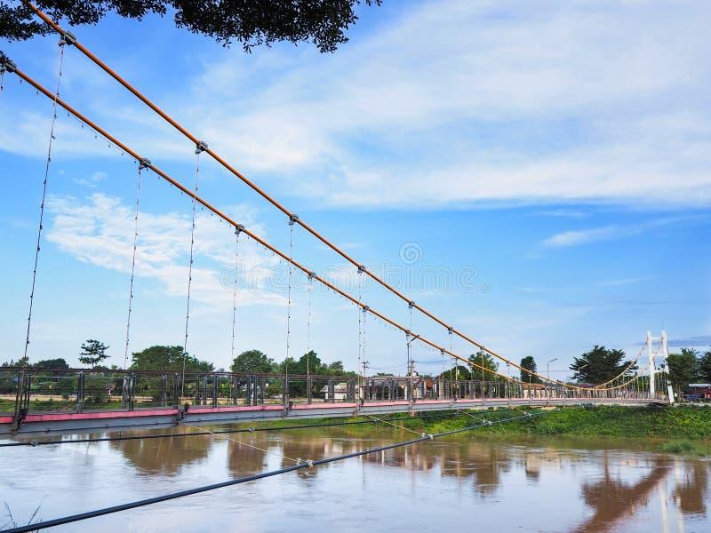 Hangbrug over rivier en blauwe hemel stock foto