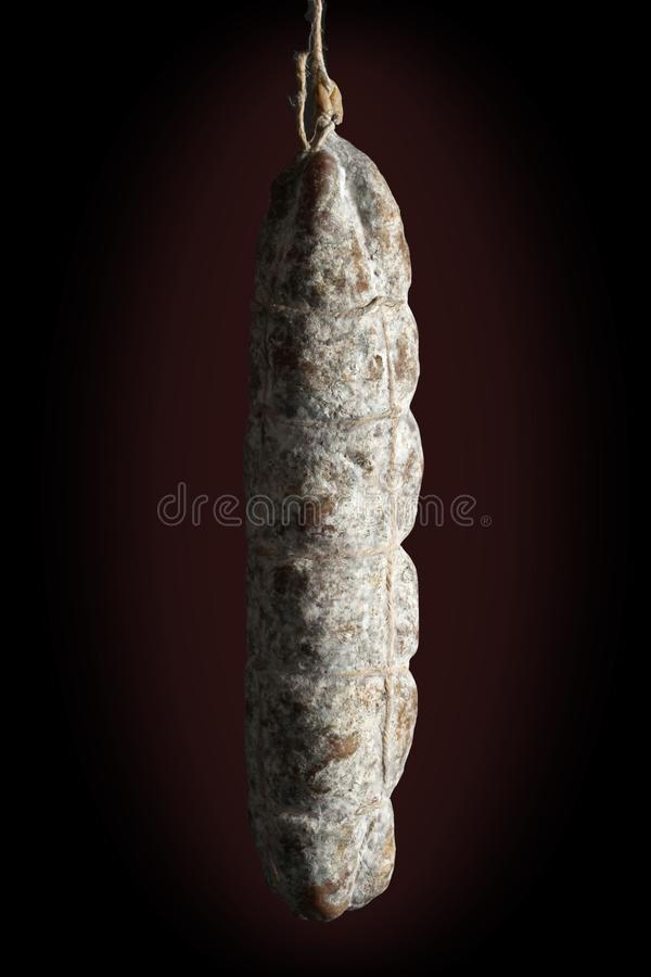 Hanged whole traditional italian salami on a balck background. Whole traditional italian salami on a balck background stock photo