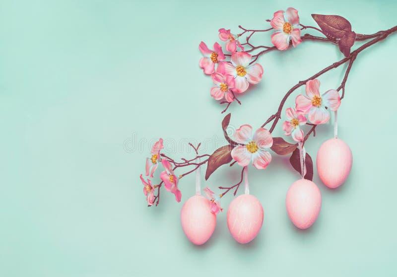 Hangen vertakken de pastelkleur roze paaseieren zichdie op de lentebloesem bij blauwe turkooise achtergrond royalty-vrije stock fotografie