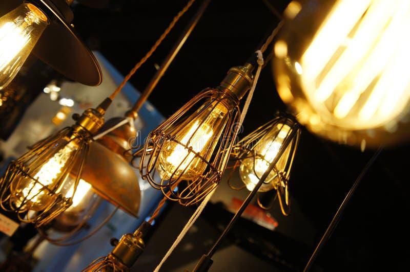 Hangende gloeilamp en koperlampen stock foto