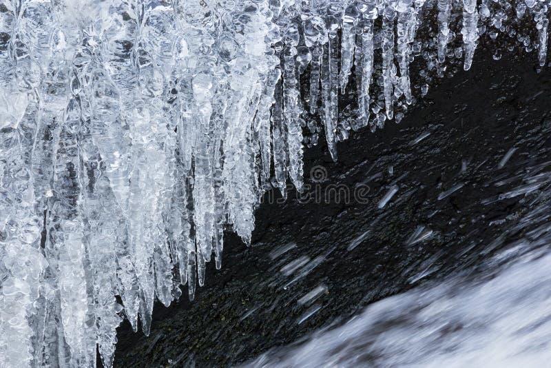 Hangende ijskegels boven stromend water in de winter royalty-vrije stock foto's