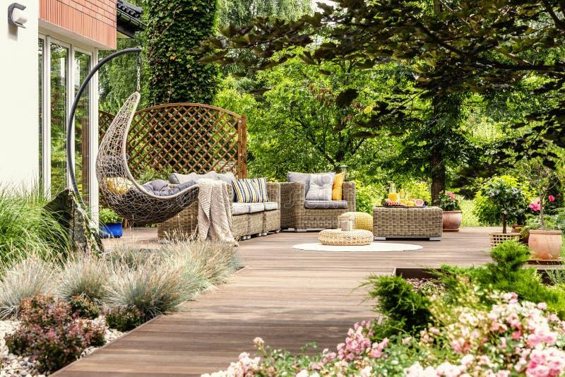 Hangende stoel en poef op houten veranda in het midden van tuin stock fotografie