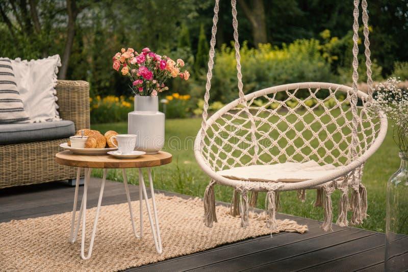 Hangende stoel naast lijst met bloemen op terras in de tuin tijdens de lente Echte foto stock fotografie