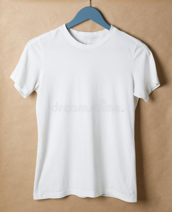 Hanger with blank white t-shirt on cardboard background royalty free stock photos