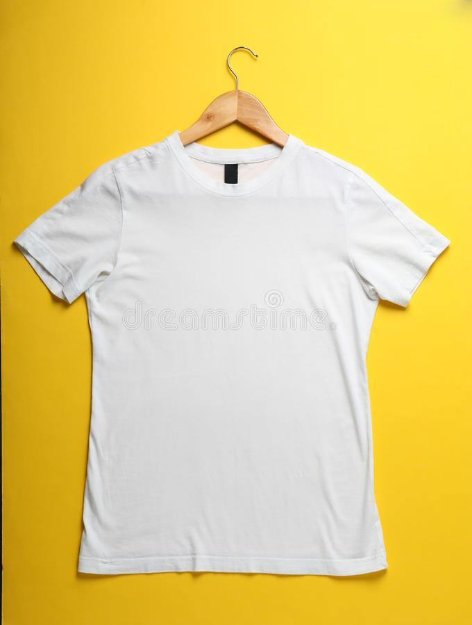 Hanger with blank white t-shirt on yellow background stock photos