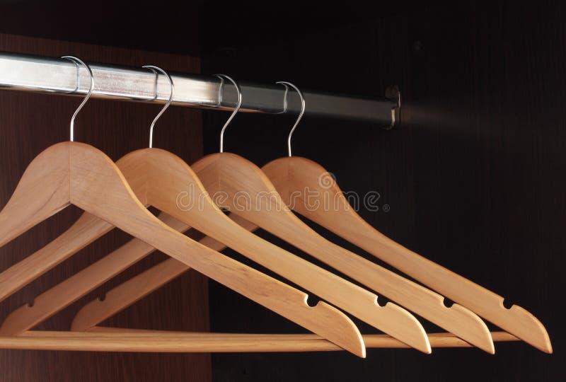 Hangers. Wooden hangers hanging in an empty closet on the upper stock photos