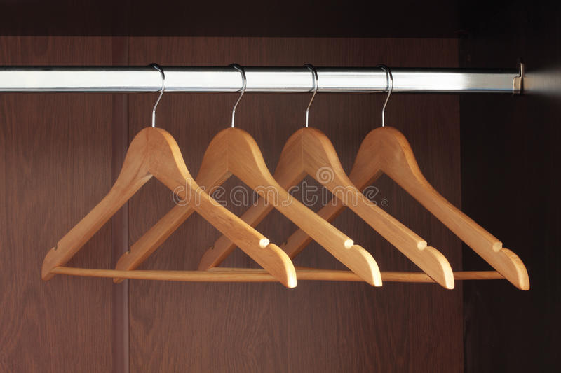 Hangers. Wooden hangers hanging in an empty closet on the upper stock photography