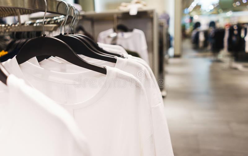 Hangers bright fashionable clothes. T-shirts, blouses and shirts on a hanger in the mall close-up. Modern show room selling clothes men, women and children royalty free stock photos