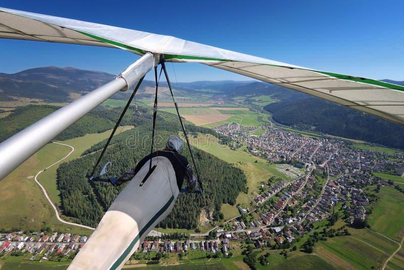 Hangglider proefvliegen over kleine stad in alpiene vallei royalty-vrije stock fotografie