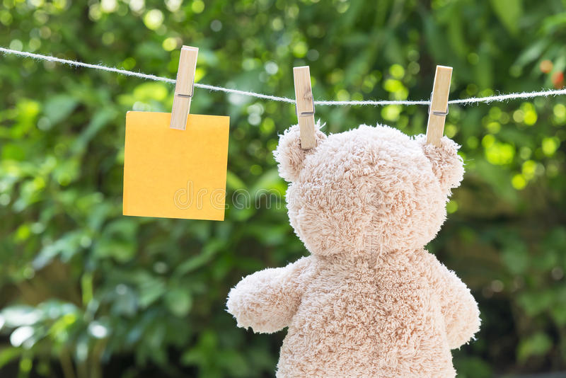 Hanging the bear doll on the clothesline stock photo