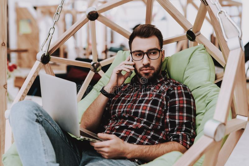 Hanging Chair. Laptop. Sit. Brainstorm. Young Guy stock photos