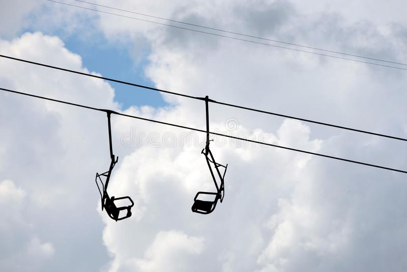 Chair lift. 2 hanging chairs at old single seat chair lift against cloudy sky royalty free stock image