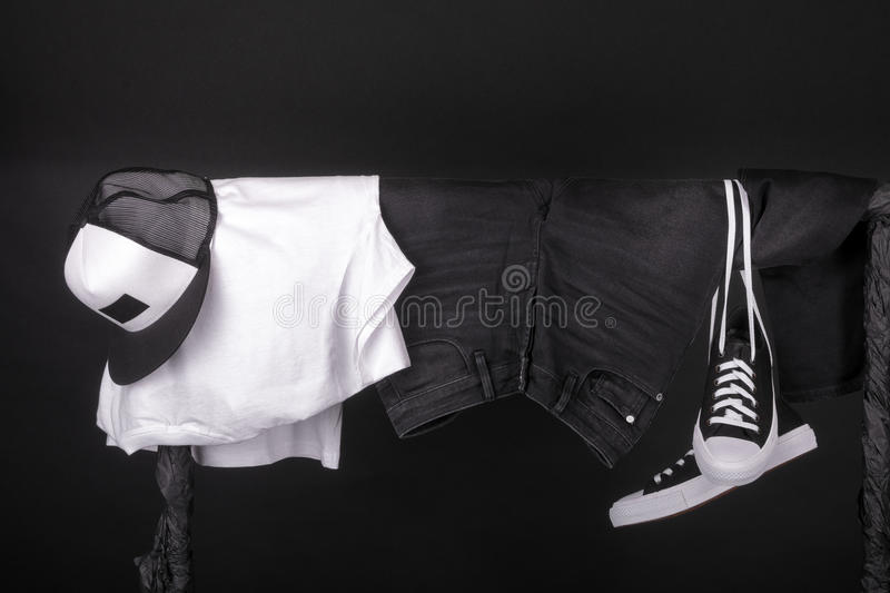 Hanging clothing. Black and white sneakers, cap jeans on clothes rack background. Copy space. Hanging clothing. Black and white sneakers, cap and jeans on stock photography