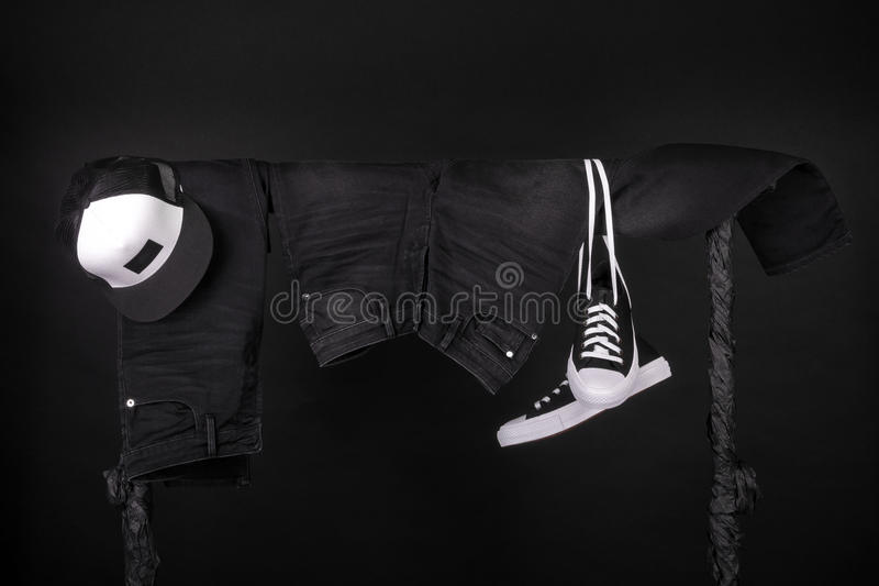 Hanging clothing. Black and white sneakers, cap jeans on clothes rack background. Copy space. Hanging clothing. Black and white sneakers, cap and jeans on stock photo