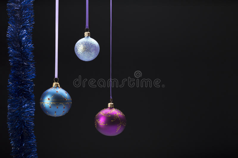 Hanging colorful christmas balls on black stock images