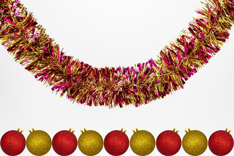Hanging colorful tinsel with red and gold Christmas baubles, isolated on a white background with copy space, christmas decorations.  royalty free stock photography