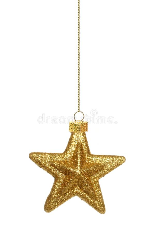 Hanging gold star Christmas ornament over white royalty free stock photography