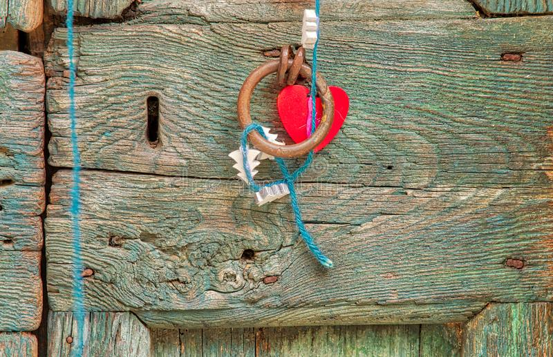 Hanging heart on old door royalty free stock images