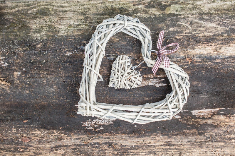 Hanging heart and wooden background in country style. stock image