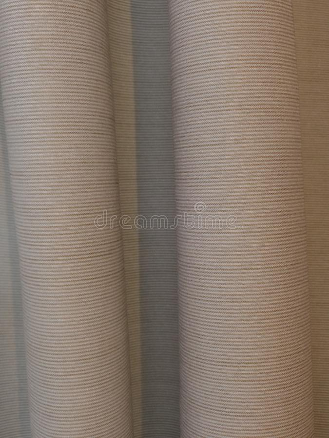 Hanging horizontally ribbed beige curtains royalty free stock photography