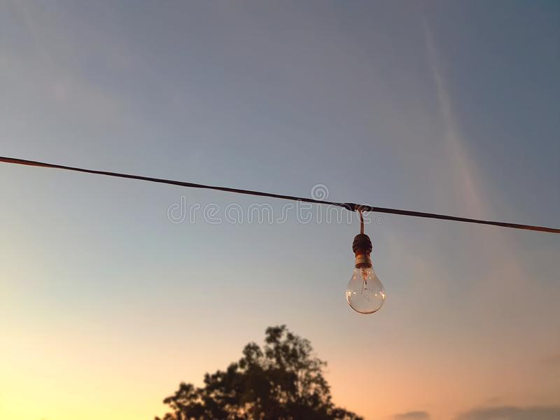 Hanging Incandescent Lamp Against Sky During Sunset royalty free stock image