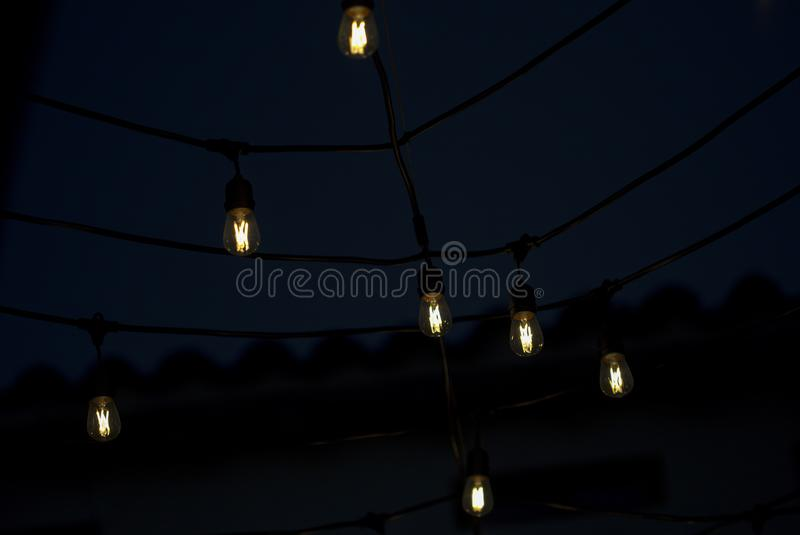 Hanging LED light bulbs switched on. Hanging LED light bulbs, switched on, used to decorate interiors or exteriors during special festivities. Captured at the stock photo