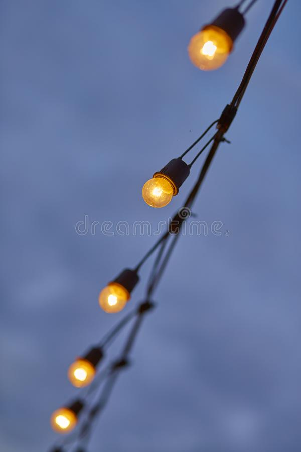 Hanging light bulb with blue sky royalty free stock photo