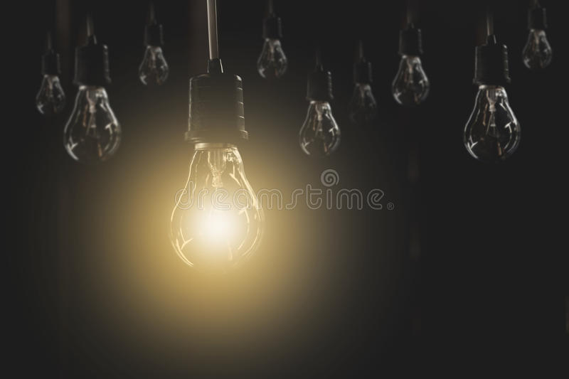 Hanging light bulbs with glowing one on dark background. Idea and creativity concept. With light bulbs stock photo