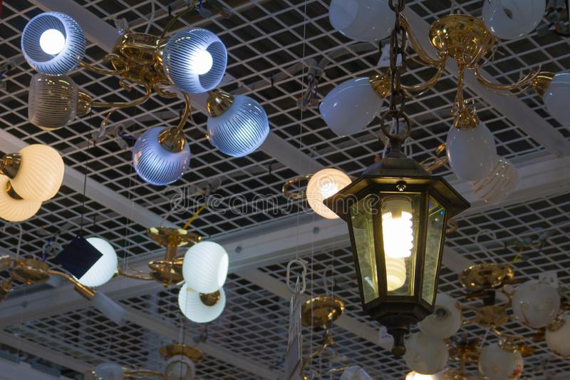 Hanging lighted bulbs in store. Hanging lighted bulbs and chandeliers in store royalty free stock images